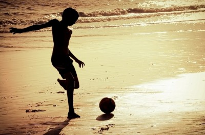 Silhouette of boy on the beach playing football